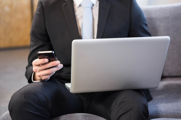 Businessman using laptop and mobile phone in office
