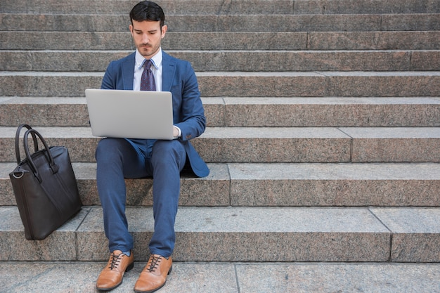 Businessman using laptop near bag