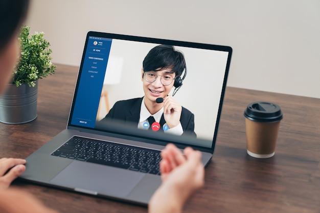 Бизнесмен, используя ноутбук на столе с видеозвонком на телефонную встречу с оператором службы поддержки клиентов.