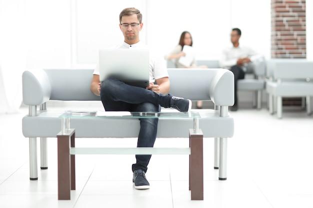 Бизнесмен, используя ноутбук, сидя в холле отеля. фото с копией пространства