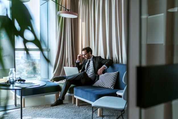 近代的なオフィスの椅子に座っている間ラップトップを使用しての実業家。