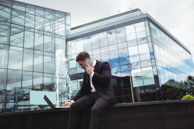 전화 통화하는 동안 노트북을 사용하는 사업