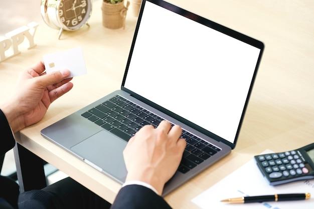 Бизнесмен, используя ноутбук с пустой экран на столе с кредитной кредитной для покупок.