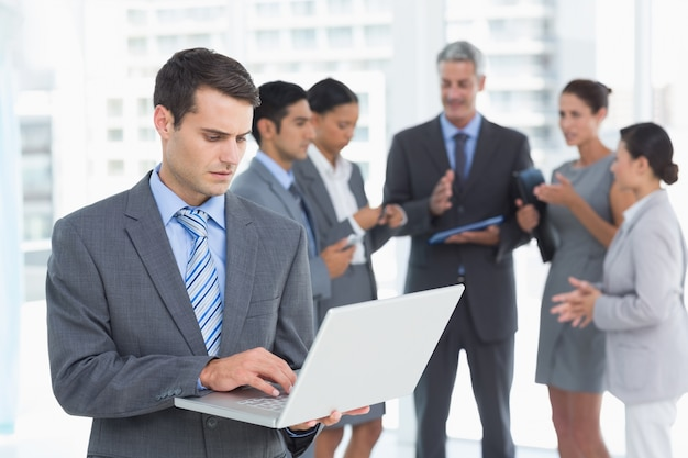Businessman using laptop with colleagues behind