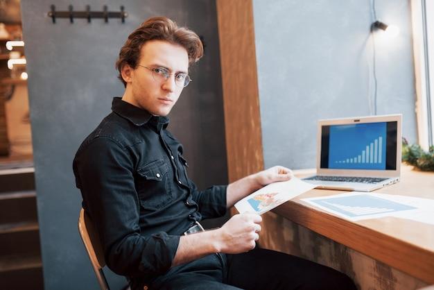 一杯のコーヒーとコーヒーショップで木製のテーブルにタブレットとペンでラップトップを使用するビジネスマン。フリーランサーとして会社をリモートで管理している起業家。