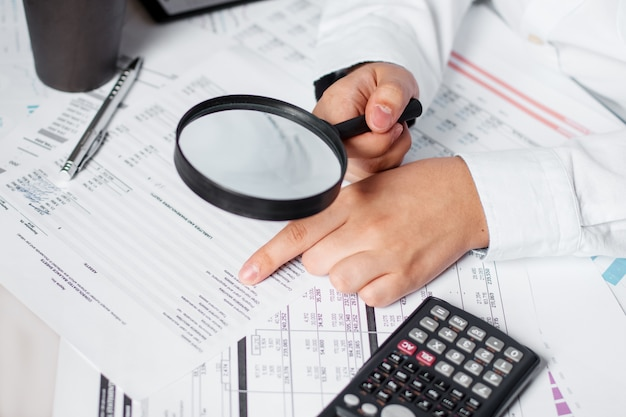 拡大鏡を使用して貸借対照表の年次を確認するビジネスマン