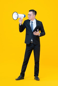 Businessman using megaphone about to say or announce something