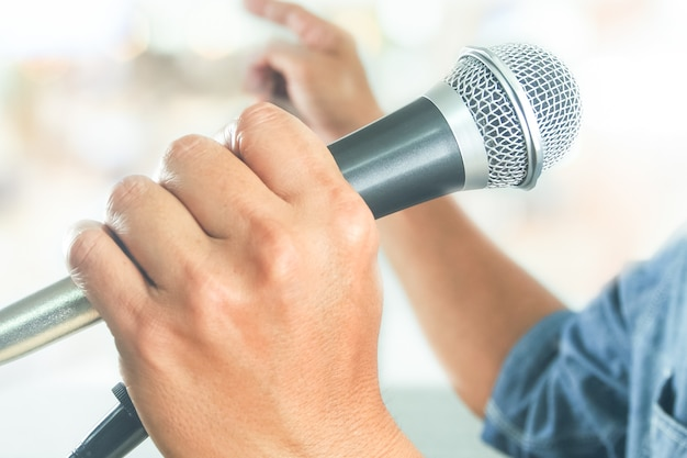 Businessman using microphone for public speaking seminar presentation