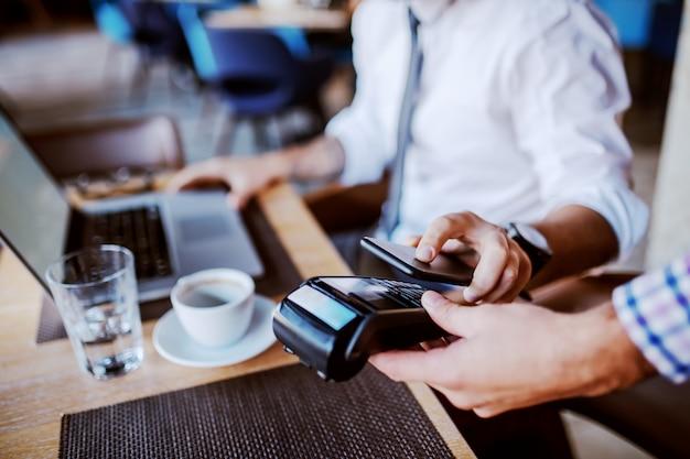 Бизнесмен с помощью технологии мобильных платежей для оплаты счета в кафе.