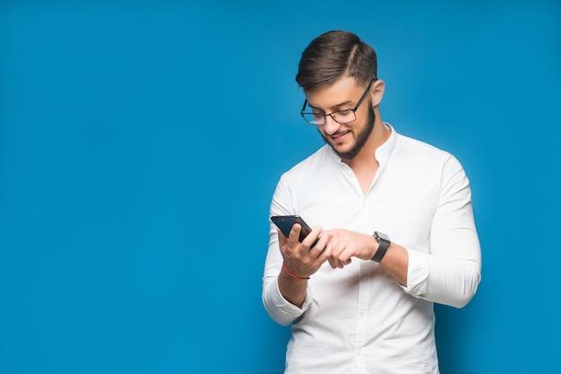 Бизнесмен с помощью приложения для мобильного телефона текстовых сообщений в синем
