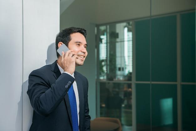 백그라운드에서 고층 빌딩이 도시 도시에서 사무실 외부의 휴대 전화 애플 리케이션 문자 메시지를 사용하는 사업가. 비즈니스 작업에 대 한 스마트 폰 들고 젊은 백인 남자.