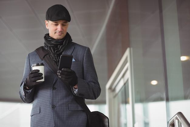 Бизнесмен с помощью мобильного телефона у входа