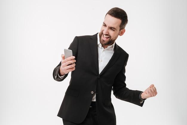 Businessman using mobile phone and make winner gesture.
