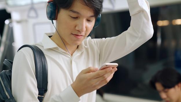 公共の電車で携帯電話を使用しているビジネスマン。アーバンシティライフスタイル通勤コンセプト。