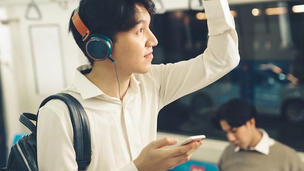 Бизнесмен с помощью мобильного телефона в общественном поезде