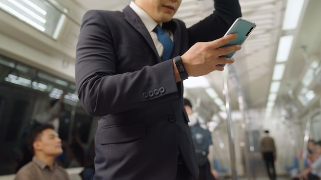 Businessman using mobile phone on public train . urban city lifestyle commuting concept .