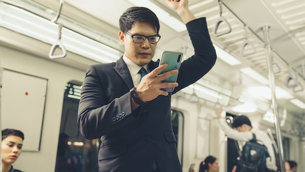 Businessman using mobile phone on public train