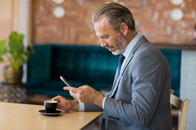 Businessman using mobile phone while having a cup of tea
