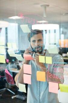 Бизнесмен с помощью мобильного телефона, глядя на клей отмечает графики на стекле