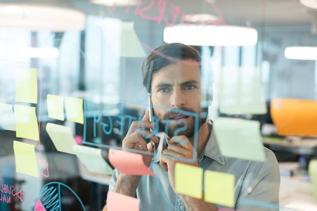 Бизнесмен с помощью мобильного телефона, глядя на планы, написанные на стекле