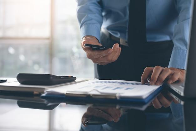Бизнесмен используя мобильный телефон пока работающ на деловом документе в офисе