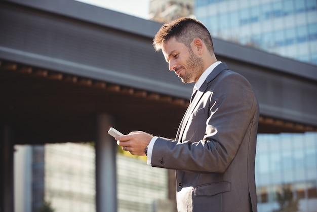 Бизнесмен с помощью мобильного телефона