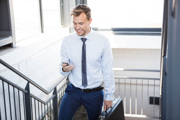 Businessman using phone and climbing staircase in office