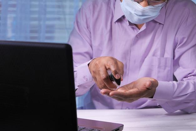 Businessman using sanitizer gel on on office desk
