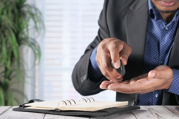 Businessman using sanitizer gel on on office desk.