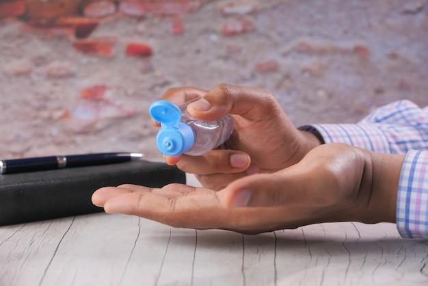 Бизнесмен, используя дезинфицирующий гель на офисном столе