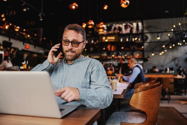 スマートフォンを使用して、バーでラップトップを指すビジネスマン。
