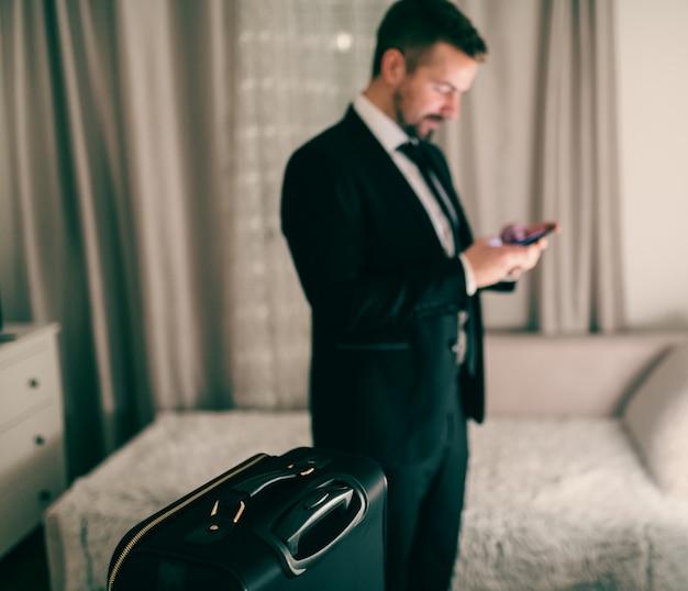 寝室に立って旅行の準備をしながらスマートフォンを使用しての実業家。スーツケースにセレクティブフォーカス。