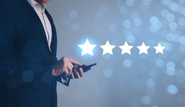 Businessman using smart phone with icon  star symbol to increase rating of company. customer service experience concept.
