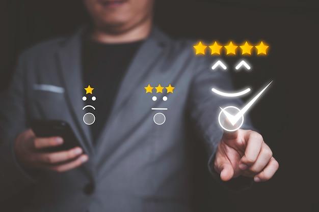 Бизнесмен, используя смартфон и нажав кнопку улыбки для лучшей оценки, концепции удовлетворенности клиентов.