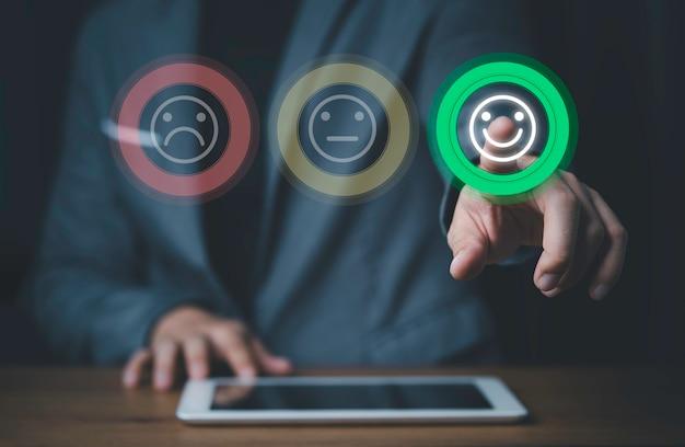 사업가 스마트 폰을 사용하고 최고의 평가, 고객 만족 개념을 위해 미소 버튼을 누르십시오.