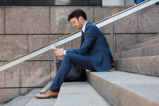 Businessman using smartphone on steps