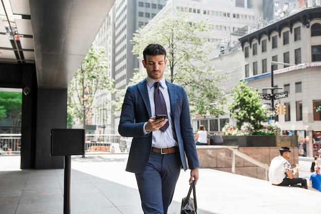 Uomo d'affari utilizzando smartphone sulla strada