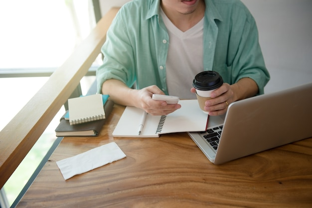 Businessman using smartphone while working with laptop keyboard on desk with coffee