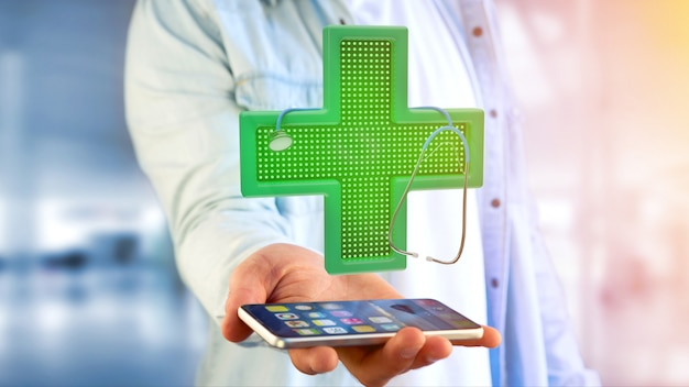 Businessman using a smartphone with a lighting pharmacy cross and a stethoscope