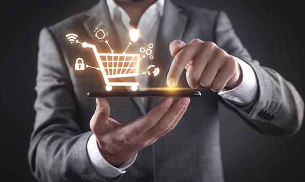 ショッピングカートでスマートフォンを使用するビジネスマン。 eコマース。オンラインショッピング