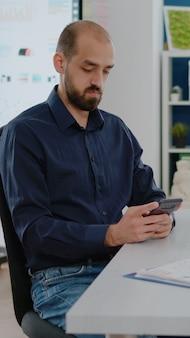 タッチスクリーンでスマートフォンを使用してビジネスマン