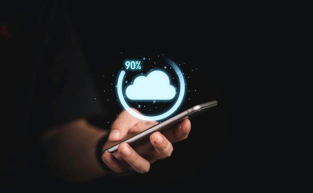 仮想クラウドコンピューティングとスマートフォンを使用しているビジネスマンと転送データ情報アップロードダウンロードアプリケーションのダウンロードパーセンテージの進捗状況。技術変革のコンセプト。