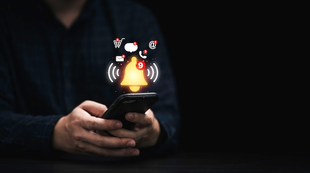アプリケーション通知アラートの概念のために仮想黄色のベルが鳴っているスマートフォンを使用しているビジネスマン。