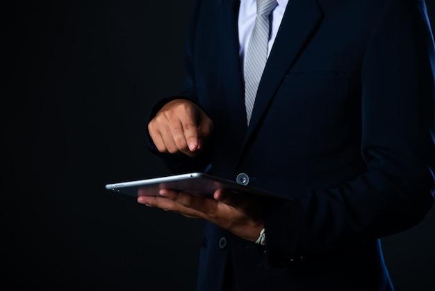 Бизнесмен используя таблетку анализируя данные по продаж и диаграмму диаграммы экономического роста, технологию