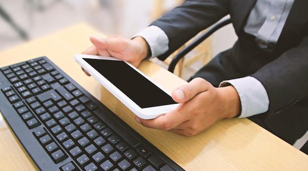 Бизнесмен с помощью планшета и компьютера.