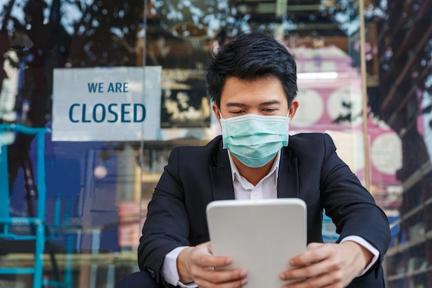 Бизнесмен с помощью планшета и медицинской маски