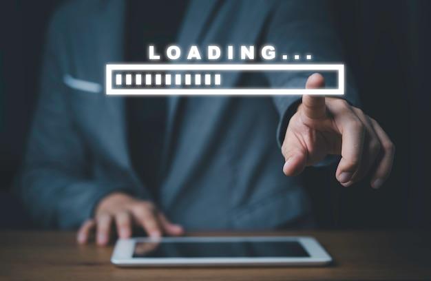 タブレットを使用して、アプリケーションと情報、技術概念をダウンロードおよびアップロードするための仮想ローディングタールに触れるビジネスマン。