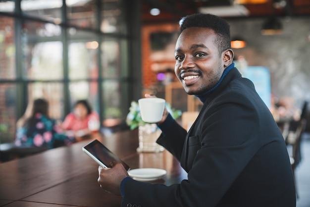 コーヒーショップでタブレットコンピューターを使用してビジネスマン