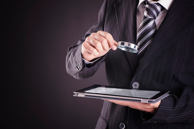 Businessman using tablet computer with magnifying glass