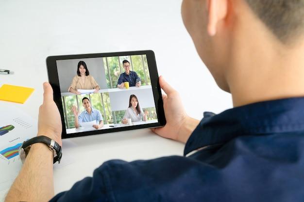 Бизнесмен с помощью планшета для видеоконференцсвязи с коллегами